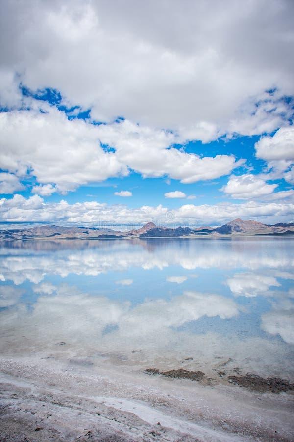 Planos de sal de Bonneville no dia ensolarado com nuvens Reflexão de espelho na água foto de stock
