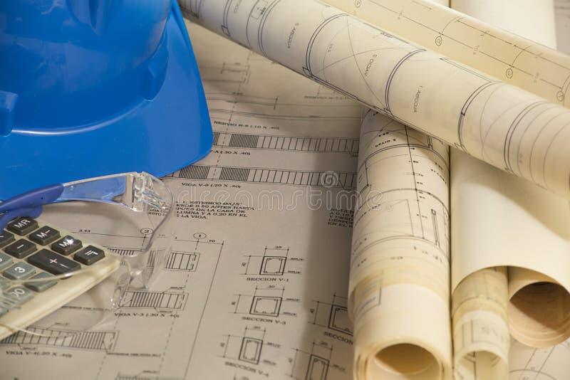 Plans architecturaux de construction - dessins architecturaux avec le casque de sécurité, les verres protecteurs et la calculatri photographie stock