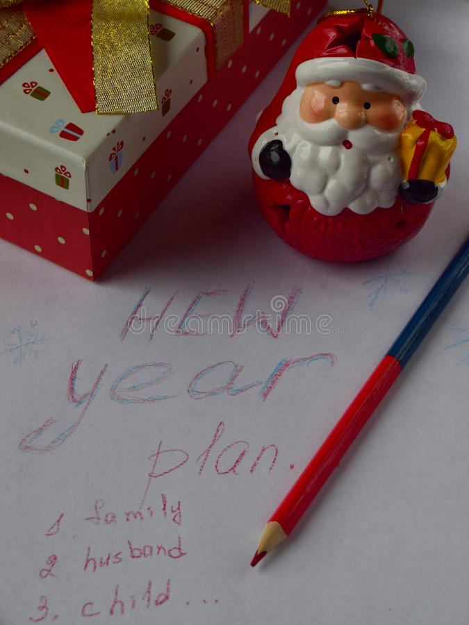 Plans for the new year written on a white piece of paper close up. Red box with a red-gold bow with a white piece of paper on which the plans for the New year stock photos