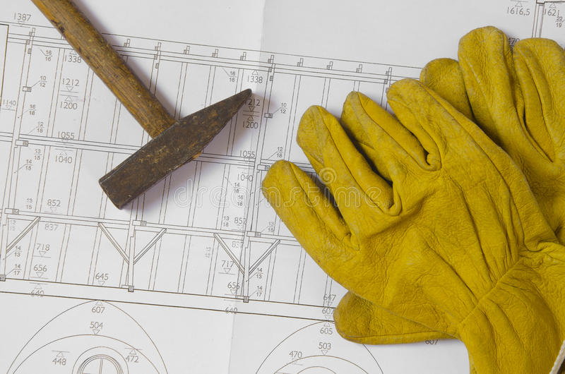 Plans and tools. Building plans with hammer and working gloves on top royalty free stock image
