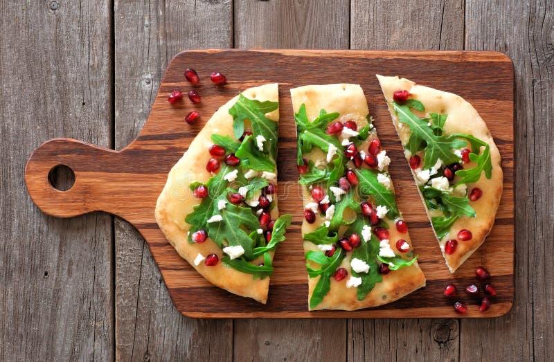 Plant bröd med granatäpplen, arugula och ost på den wood serveren royaltyfri fotografi