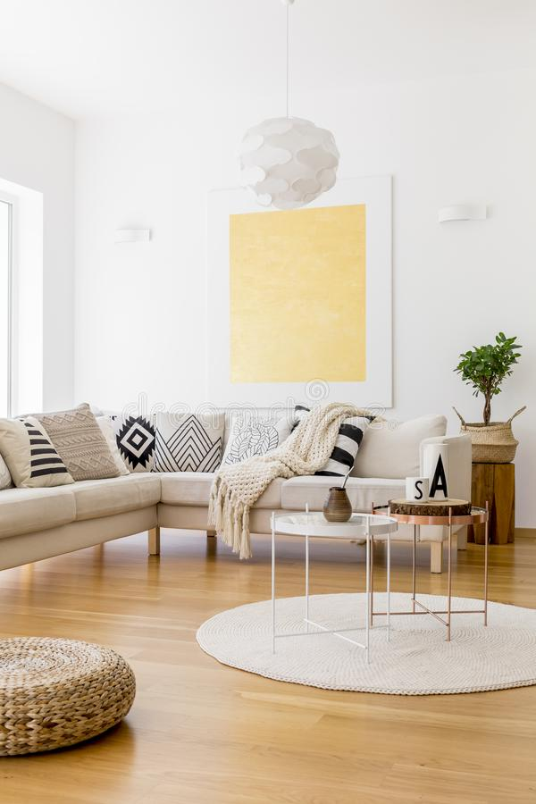 Plant in braided basket. On wooden stool in living room with gold painting on white wall stock images