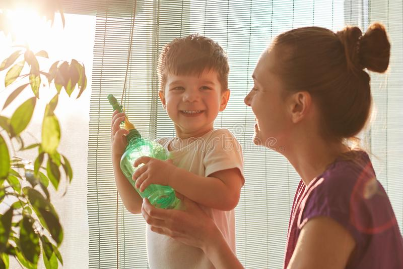 Plant care concept. Cheerful little male kid holds spray bottle, wants to water flower, stands neear his affectionate mother near stock photos