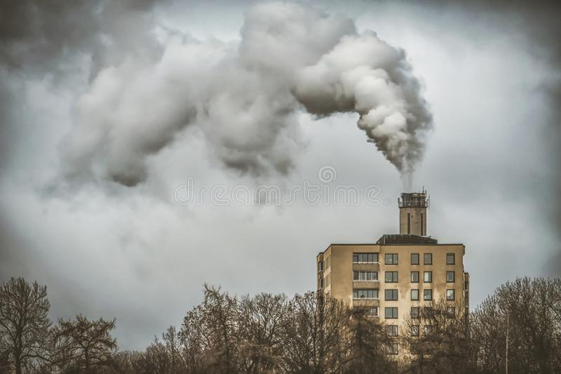 The plant emits pollutants into the atmosphere, from the factory pipes comes out a thick smoke. Behind the apartments building air pollution smog city royalty free stock photography