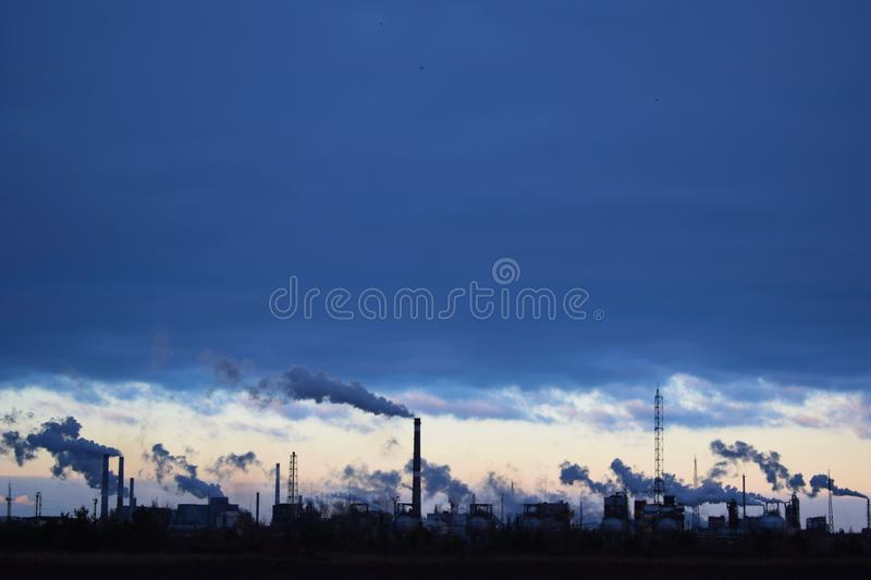 Metallurgical industry against the sky. The plant emits smoke and smog from the pipes at sunset, pollutants enter the atmosphere. Environmental disaster stock photo