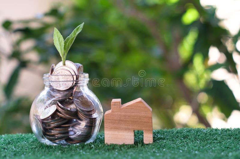 Plant growing from coins in glass jar. Wooden house model on artificial grass. Home mortgage and property investment concept royalty free stock image