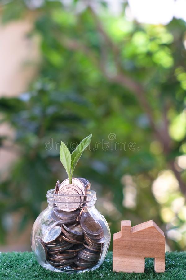 Plant growing from coins in glass jar. Wooden house model on artificial grass. Home mortgage and property investment concept royalty free stock photos