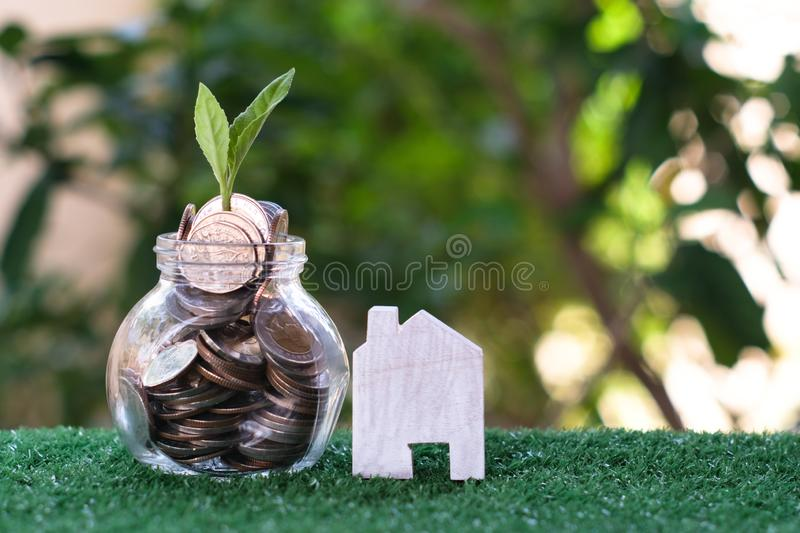 Plant growing from coins in glass jar. Wooden house model on artificial grass. Home mortgage and property investment concept stock photos