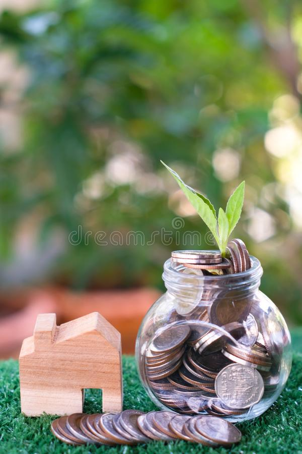 Plant growing from coins in glass jar. Wooden house model on artificial grass. Home mortgage and property investment concept royalty free stock photography