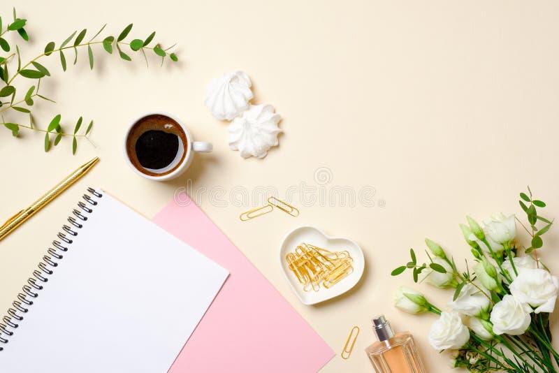 Plant lekmanna- inrikesdepartementetskrivbord, bästa sikt Kvinnlig tillbehör på pastellfärgad beige bakgrund Kaffekopp, pappersno fotografering för bildbyråer