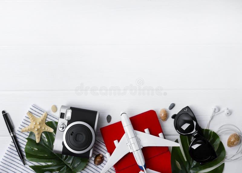 Plant lekmanna- loppbegrepp: stadsplanerare, pass, smartphone, kamera, penna, stj?rnafisk och monsterasidor p? tr?bakgrund arkivfoto