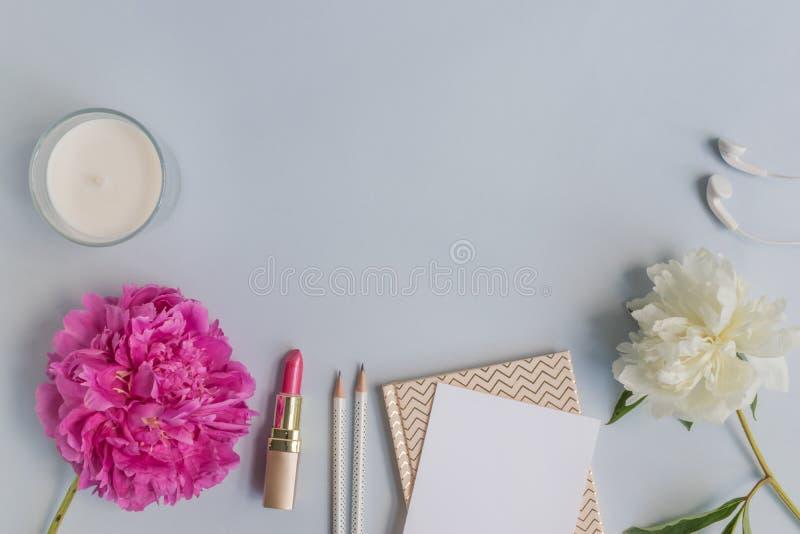 Plant lekmanna- skrivbord med den rosa pionen, sk?nhetsmedel och tillbeh?r royaltyfria bilder