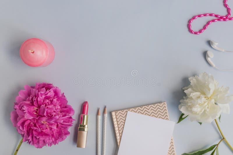 Plant lekmanna- skrivbord med den rosa pionen, sk?nhetsmedel och tillbeh?r arkivbild