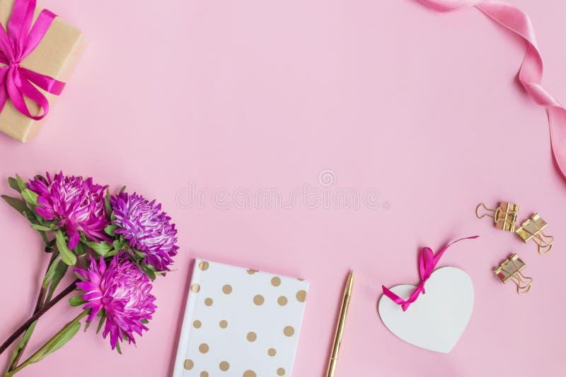 Plant lekmanna- skrivbord med rosa blommor, anteckningsboken och vit hjärta royaltyfri fotografi