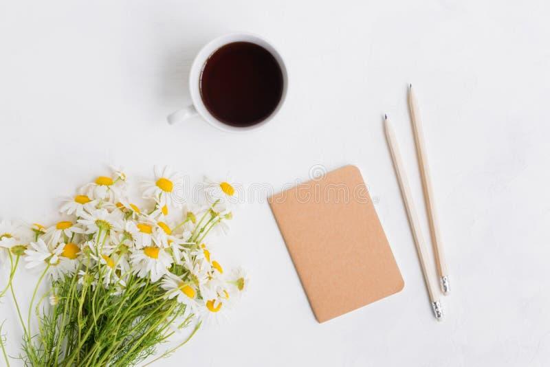 Plant lekmanna- skrivbord med vita tusensk?nor, anteckningsboken och koppen med te royaltyfri bild