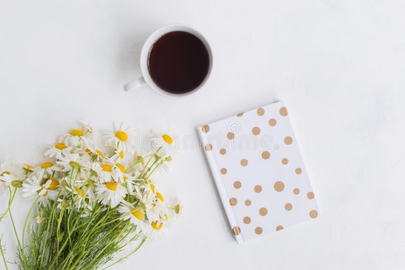Plant lekmanna- skrivbord med vita tusensk?nor, anteckningsboken och koppen med te royaltyfria bilder
