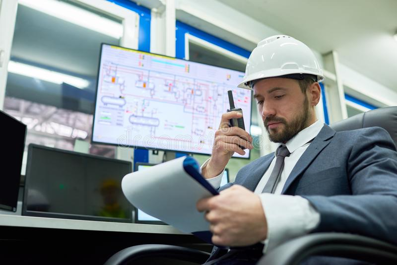 Plant Manager Giving Instructions from Office. Portrait of bearded businessman wearing hardhat overseeing plant production process while sitting at desk in royalty free stock image