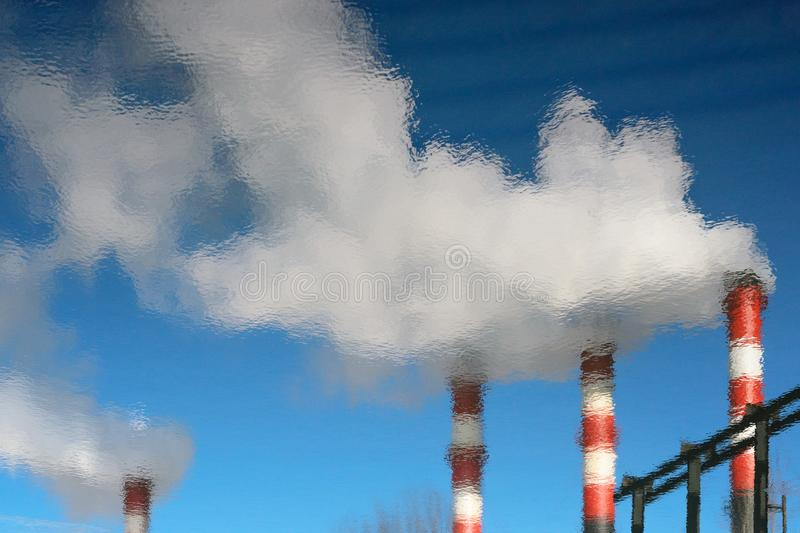 Plant pipes with smoke in the reflection of water. The smoking chimneys of the plant are reflected in the water. Plant pipes with smoke against clear blue sky royalty free stock photos