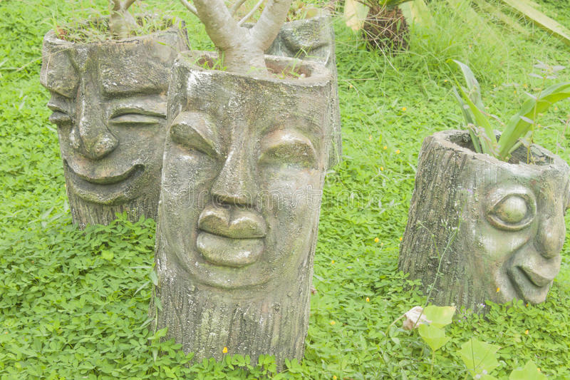 Plant pot. A face carved in a few vietnamese plant pots, made of stone stock photos