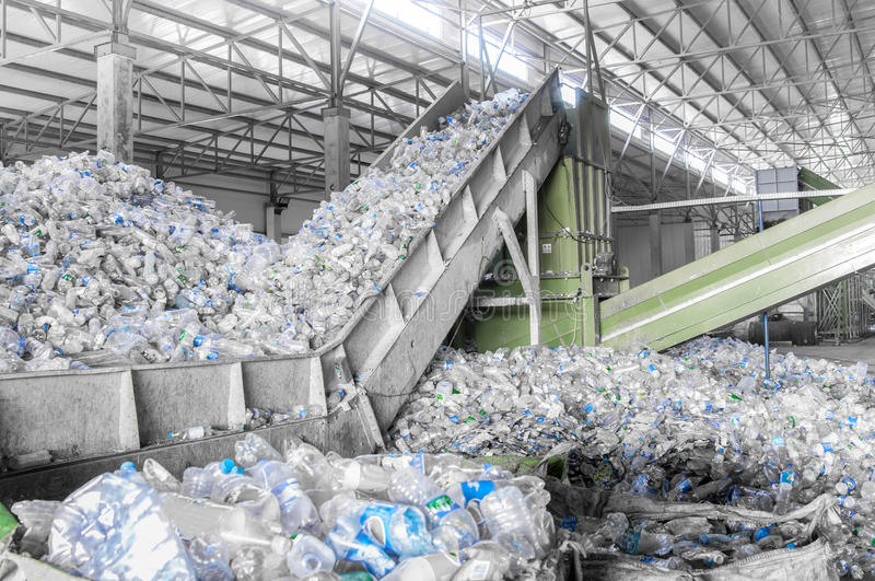 A plant for recycling bottles. Closeup escalator with a pile of plastic bottles at the factory for processing and recycling. PET recycling plant stock image