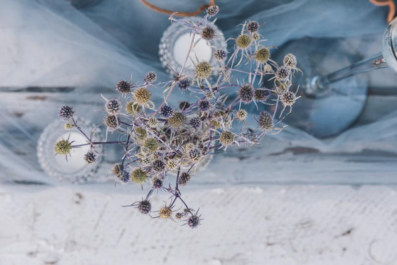 Plant, tea candles and sheer blue fabric as part of wedding table setup stock photos