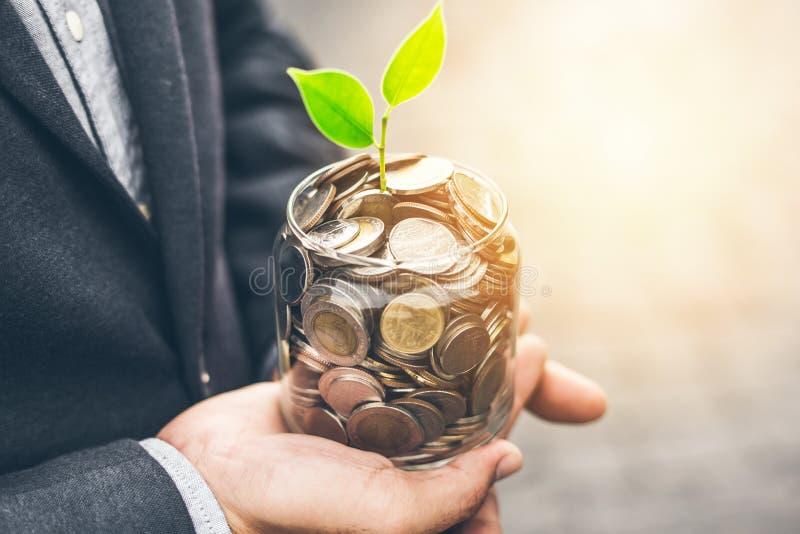 Planta creciente de la cubierta del hombre de negocios con el dinero de la moneda imagen de archivo