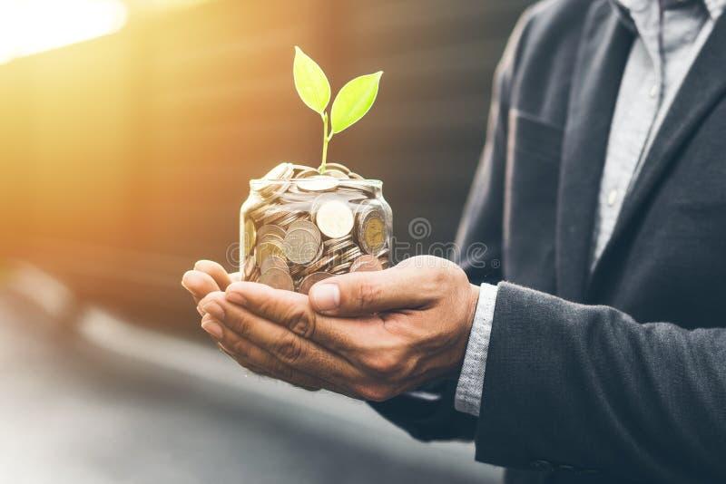 Planta creciente de la cubierta del hombre de negocios con el dinero de la moneda fotografía de archivo