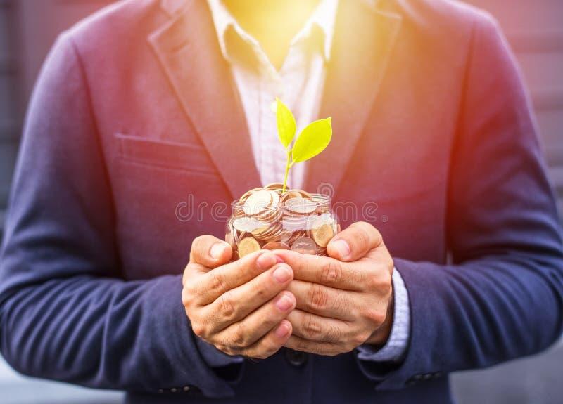Planta creciente de la cubierta del hombre de negocios con el dinero de la moneda foto de archivo libre de regalías