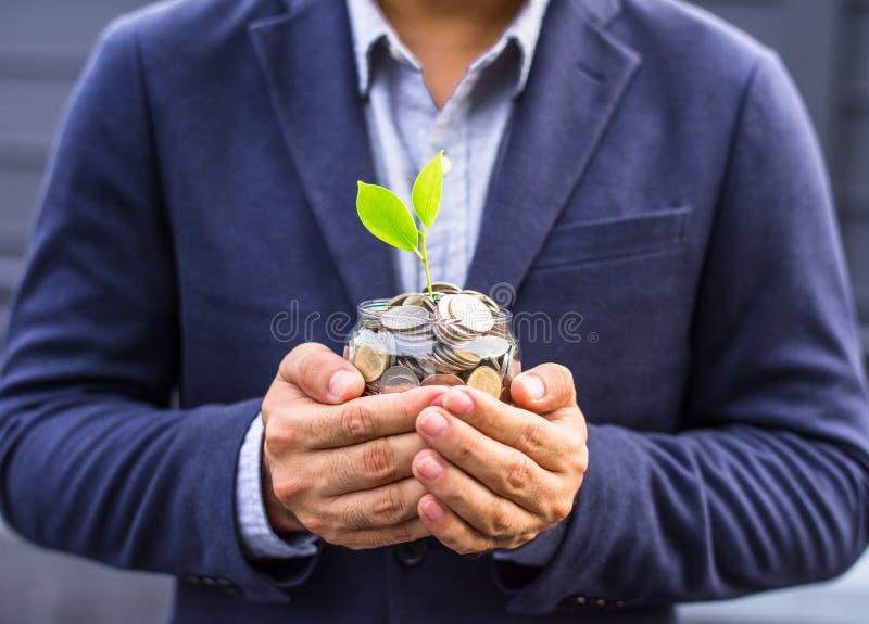 Planta creciente de la cubierta del hombre de negocios con el dinero de la moneda fotos de archivo