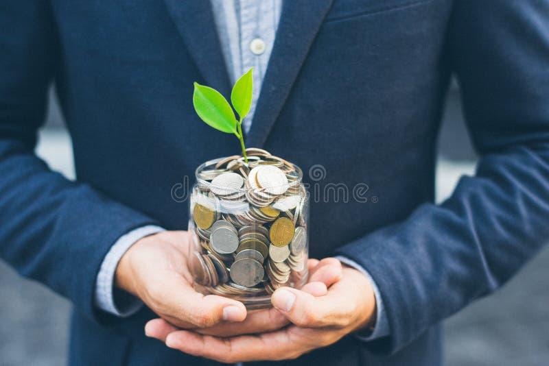 Planta creciente de la cubierta del hombre de negocios con el dinero de la moneda fotografía de archivo libre de regalías