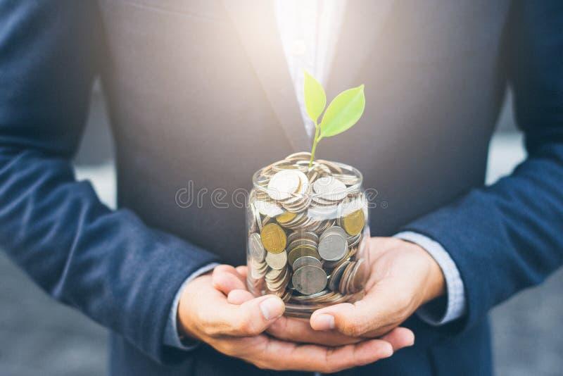 Planta creciente de la cubierta del hombre de negocios con el dinero de la moneda imagen de archivo libre de regalías