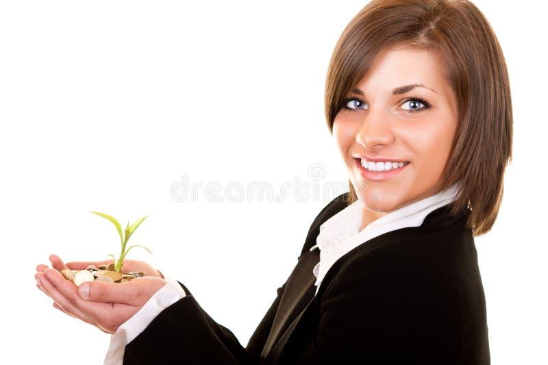 Planta crescente com moedas à disposicão imagens de stock