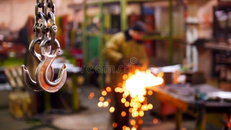 Planta da construção Uma corrente de levantamento industrial grande com um gancho na extremidade que pendura no ar Um homem que s fotografia de stock