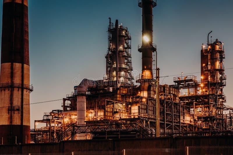 Planta da refinação de óleo na noite com luzes Encanamentos e chaminés de aço Conceito da produção do petróleo e da indústria ene imagens de stock