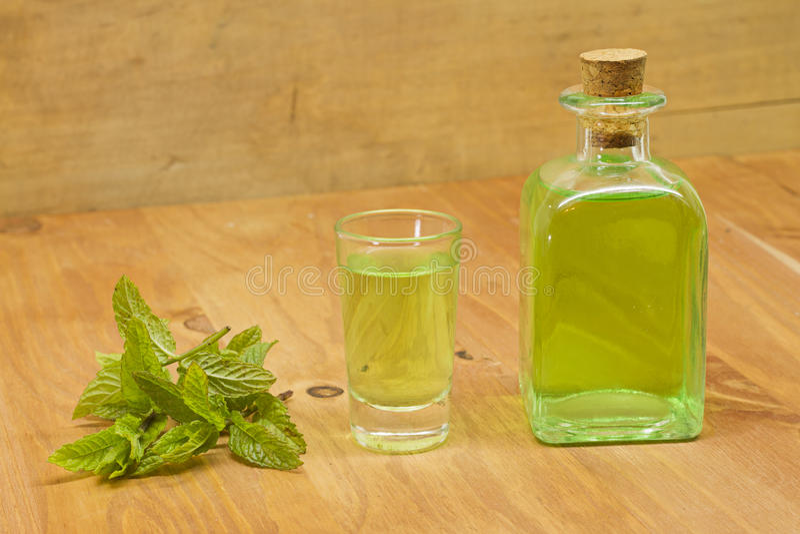 Planta de la hierbabuena, botella del licor y tiro fotos de archivo