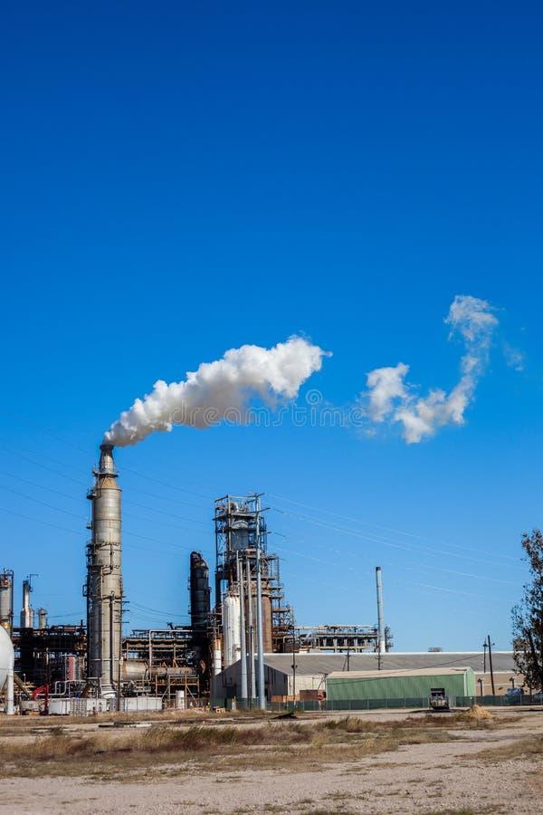 Planta de la refinería de petróleo con humo que sopla de la chimenea contra un cielo azul claro imagenes de archivo