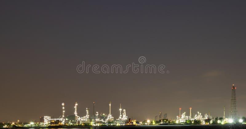 Planta de refinería larga del petróleo crudo de la foto de la noche de la exposición y mucho chimenea con el buque petroquímico d fotografía de archivo libre de regalías