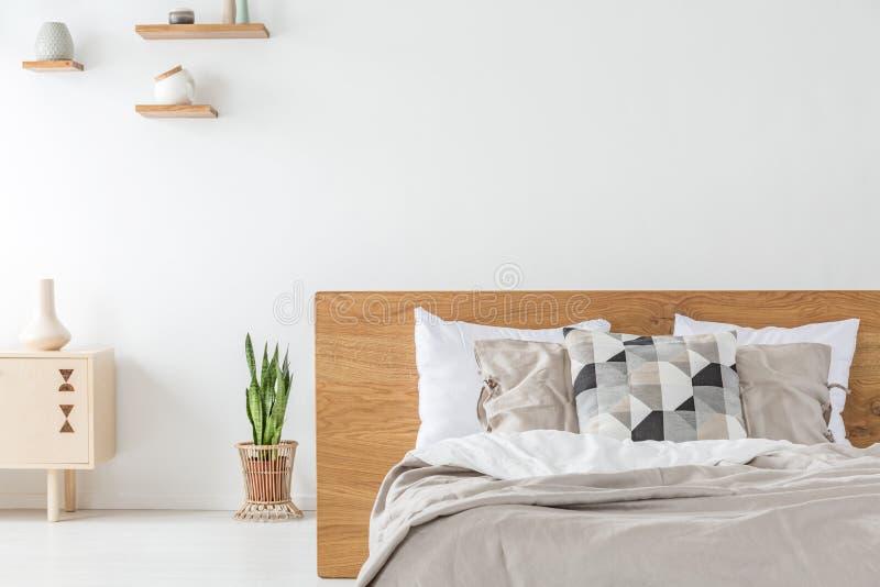 Planta entre el armario y la cama de madera con las almohadas en el interior blanco del dormitorio Foto verdadera fotos de archivo libres de regalías