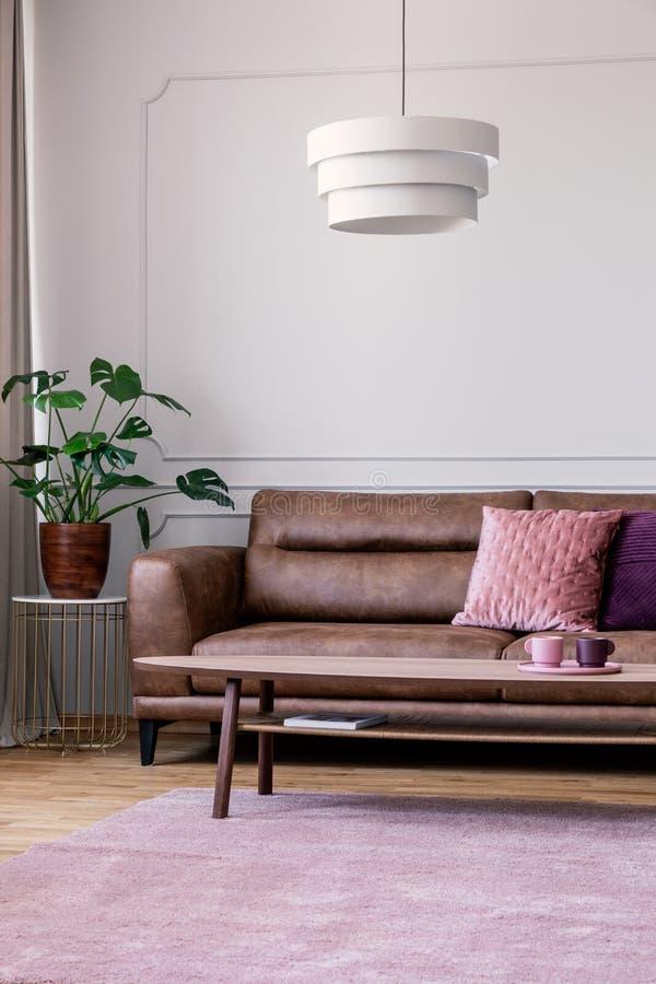 Planta na tabela ao lado do sofá de couro no interior da sala de visitas do vintage com a lâmpada acima do tapete fotos de stock royalty free