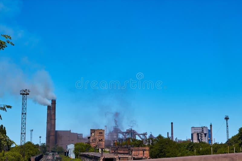 A planta polui o ambiente Poluição ambiental da planta da natureza Uma fábrica com as tubulações de fumo perto da água emissão fotografia de stock