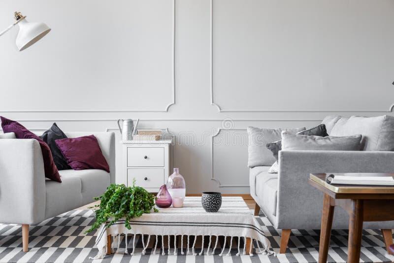 Planta verde, floreros de cristal y taza de café doted en la mesa de centro en sala de estar escandinava con la pared gris brilla foto de archivo