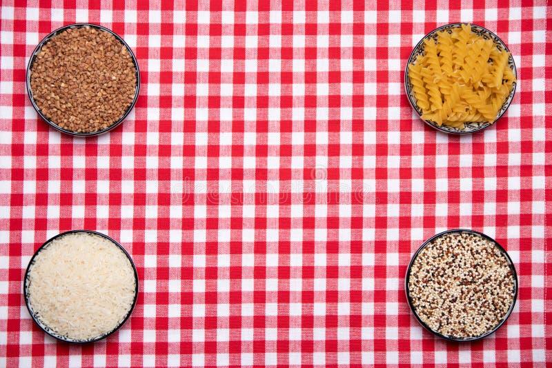 Plantaardig voedsel Een kader van vier kommen met boekweit, noedels, rijst en quinoa op een rood geruit tafelkleed Het gezonde Et stock afbeelding