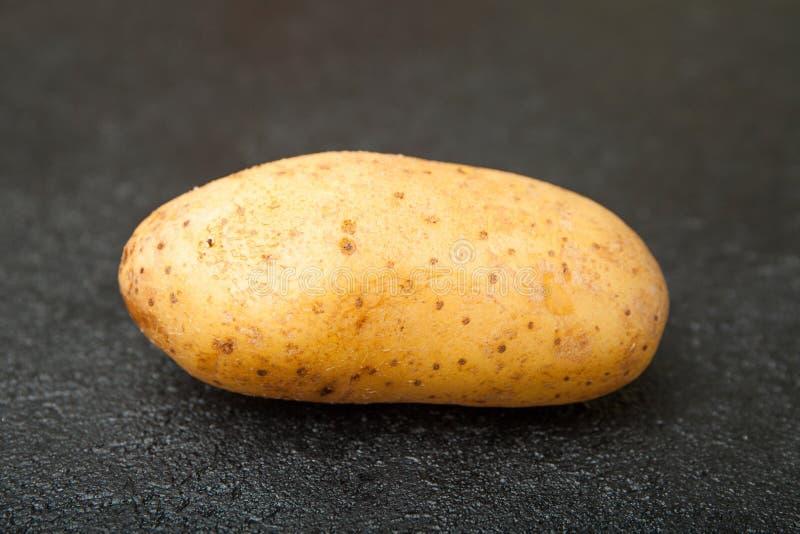 Plantaardige aardappels op een zwarte lijst Close-up royalty-vrije stock afbeelding