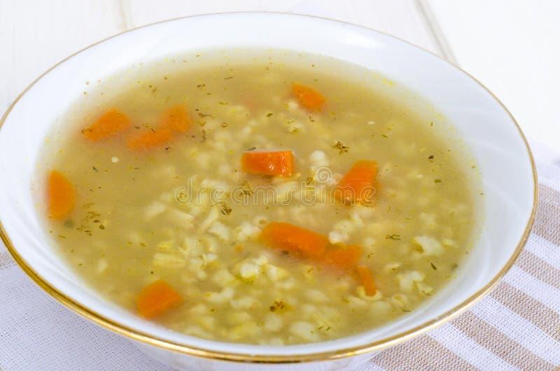 Plantaardige bouillon met ongepelde rijst en wortelen stock fotografie
