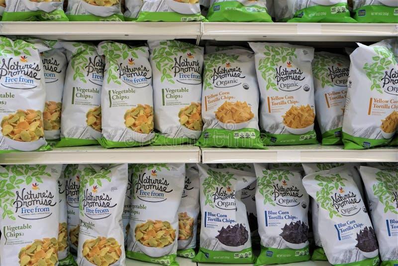 Plantaardige de Spaanderszakken van aardpromis op supermarktplank stock afbeelding
