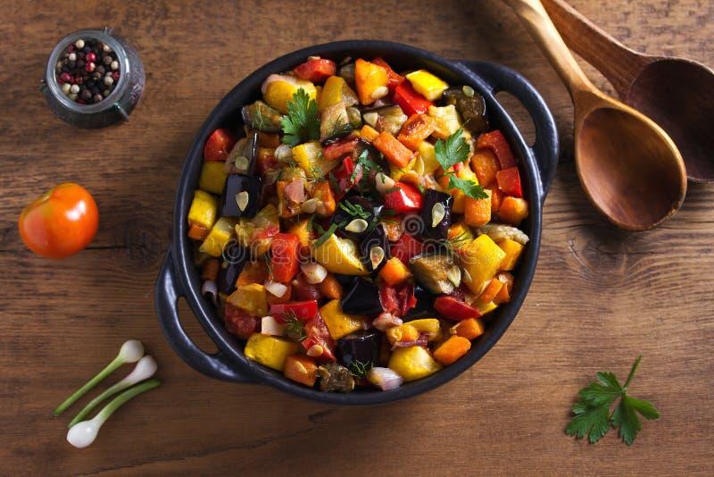 Plantaardige hutspot: aubergine, peper, tomaat, courgette, wortel en ui Gestoofde plantaardige salade stock foto's