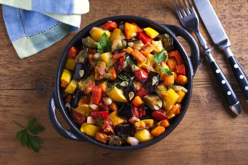 Plantaardige hutspot: aubergine, peper, tomaat, courgette, wortel en ui Gestoofde plantaardige salade stock afbeeldingen