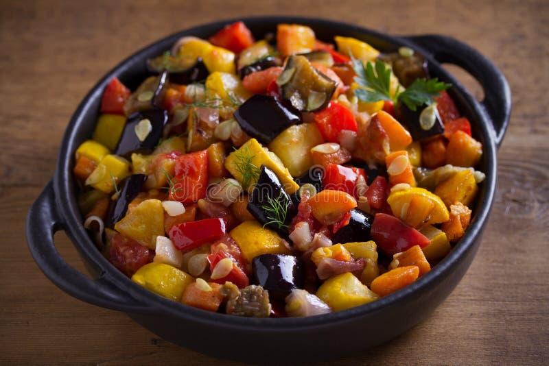 Plantaardige hutspot: aubergines, paprikapeper, tomaten, courgette, wortelen en uien Gestoofde plantaardige salade stock foto's