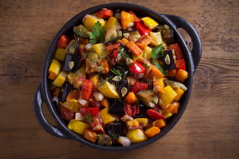 Plantaardige hutspot: aubergines, paprikapeper, tomaten, courgette, wortelen en uien Gestoofde plantaardige salade stock afbeeldingen