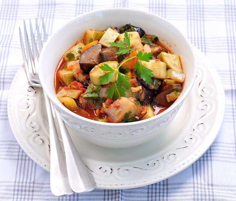 Plantaardige hutspot van aubergine, courgette, uien, wortelen, tomaten, knoflook en peterselie stock foto